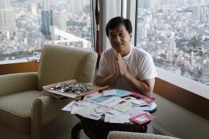 Jack Chan no hotel em Tokyo lendo as cartas dos fãs japas! Foto do Twitter do CHan